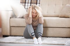 Middle aged barefoot woman sitting at the floor embracing her knees, near sofa at home, her head down, bored, troubled. Depression. Middle aged barefoot woman royalty free stock photography