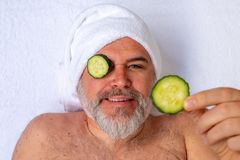 A man with cucumber slices over his eyes makes a funny gesture while receiving a beauty treatment in a salon. stock photo
