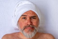 Man prepared to receive a beauty treatment with an expression of strangeness or surprise on the face stock photo