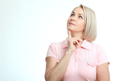 Middle-aged beautiful woman looking up thinking and dreaming isolated on white background Stock Image