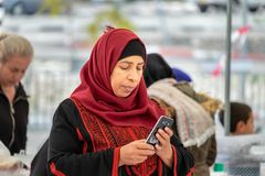 Middle aged bedouin woman in traditional arabian headdress read message on mobile phone royalty free stock photo
