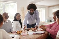 Middle aged black man bringing roast meat to the table for the Sunday family dinner with his partner, kids and their grandparents, royalty free stock image