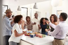 Middle aged African American  man opening champagne to celebrate at home with his three generation family stock image