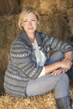 Middle Aged Blond Woman Sitting on Hay Bale. Attractive middle aged blond woman sitting on a hay bale in a barn wearing boots Stock Photos
