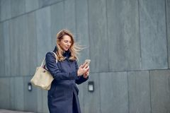 Middle-aged blond woman walking in the wind. Down an urban street alongside a grey wall with her hair blowing in the breeze reading a text message on her mobile stock images