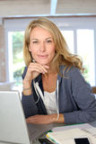 Middle-aged blond woman working on laptop Royalty Free Stock Photo
