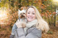 Middle aged blonde woman outdoors in autumn park garden with little dog in arms. Smiling middle aged blonde woman outdoors in autumn park garden with little dog royalty free stock photos
