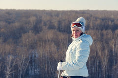 Middle-aged brunette on a hillside in a cap and ski goggles Stock Image