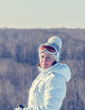 Middle-aged brunette on a hillside in a cap and ski goggles Royalty Free Stock Photos