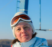 Middle-aged brunette on a hillside in a cap and ski goggles Stock Images