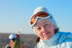 Middle-aged brunette on a hillside in a cap and ski goggles Stock Photo