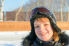 Middle-aged brunette on a hillside in a cap and ski goggles Stock Photography