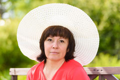 A middle-aged brunette white hat. Middle-aged woman brunette in a big white hat and red T-shirt stock photography