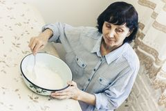 Middle-aged brunette woman kneading making dough for dumplings in blue bowl.  royalty free stock photos