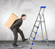 Middle aged business man with difficult task. Going up ladder Royalty Free Stock Image