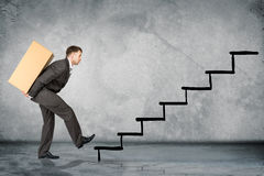 Middle aged business man with difficult task. Going up stairs Stock Photography