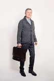 Middle Aged Business Man Holding a Brown Leather Briefcase royalty free stock images