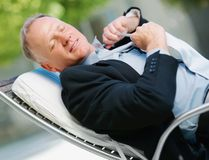 Middle aged business man relaxing on a recliner Stock Images