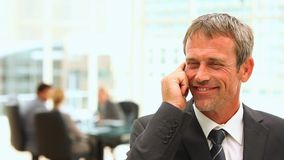 Middle aged business man talking on the phone stock footage