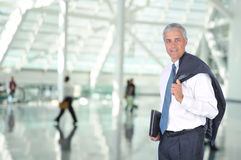 Middle Aged Business Traveler in Airport Concourse. With blurred travelers in background Royalty Free Stock Photography