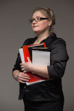 A middle-aged business woman in glasses with documents and a not Royalty Free Stock Images