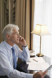 Middle Aged Businessman On Call At Desk Stock Photography