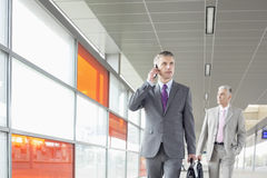 Middle aged businessman on call while walking in railroad station Royalty Free Stock Photos
