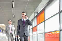 Middle aged businessman on call while walking in railroad station Royalty Free Stock Photo