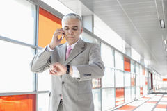 Middle aged businessman checking time while on call at railroad station Royalty Free Stock Images