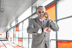 Middle aged businessman checking time while on call at railroad station Stock Photo
