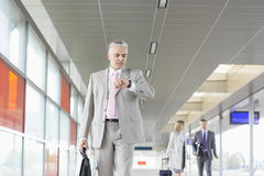 Middle aged businessman checking time with colleagues in background at railroad station Stock Photography