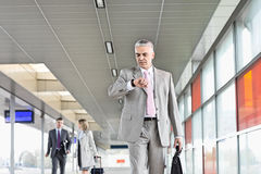 Middle aged businessman checking time with colleagues in background at railroad station Stock Photos