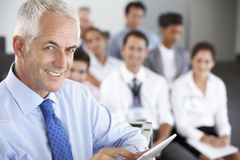 Middle Aged Businessman Delivering Presentation At Conference Stock Images