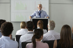 Middle Aged Businessman Delivering Presentation At Conference Stock Photo