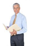 Middle aged businessman with file folder. Middle aged businessman standing and holding a manila file folder. Vertical format isolated on white background Royalty Free Stock Photo