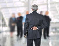 Middle aged Businessman fingers crossed behind. Standing Middle aged Businessman with fingers crossed behind back. He is standing in front of an out of focus Stock Images