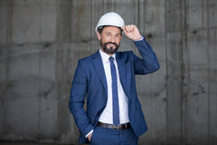 Middle aged businessman in hard hat and suit standing and smiling at work Stock Photography