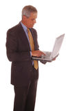 Middle Aged Businessman Holding Computer Stock Photography