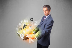 Middle aged businessman holding laptop with colorful letters Stock Photo