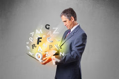Middle aged businessman holding laptop with colorful letters Royalty Free Stock Image