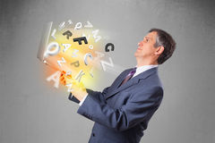 Middle aged businessman holding laptop with colorful letters Stock Photos