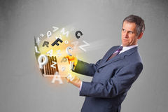 Middle aged businessman holding laptop with colorful letters Stock Photography