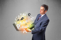 Middle aged businessman holding laptop with colorful letters Royalty Free Stock Photography