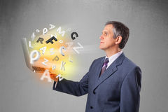 Middle aged businessman holding laptop with colorful letters Stock Image