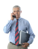 Middle aged Businessman with laptop and cell phone Stock Images