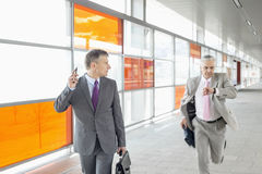 Middle aged businessman looking at colleague running in railroad station Royalty Free Stock Photo