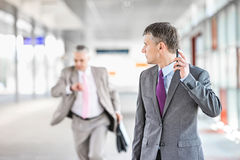 Middle aged businessman looking at colleague running in railroad station Stock Photography