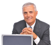 Middle aged Businessman Looking over top of laptop Royalty Free Stock Image