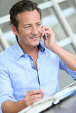 Middle-aged businessman making contracts on the phone Stock Photos