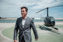 Businessman near private helicopter. Middle aged businessman near helicopter Stock Photography